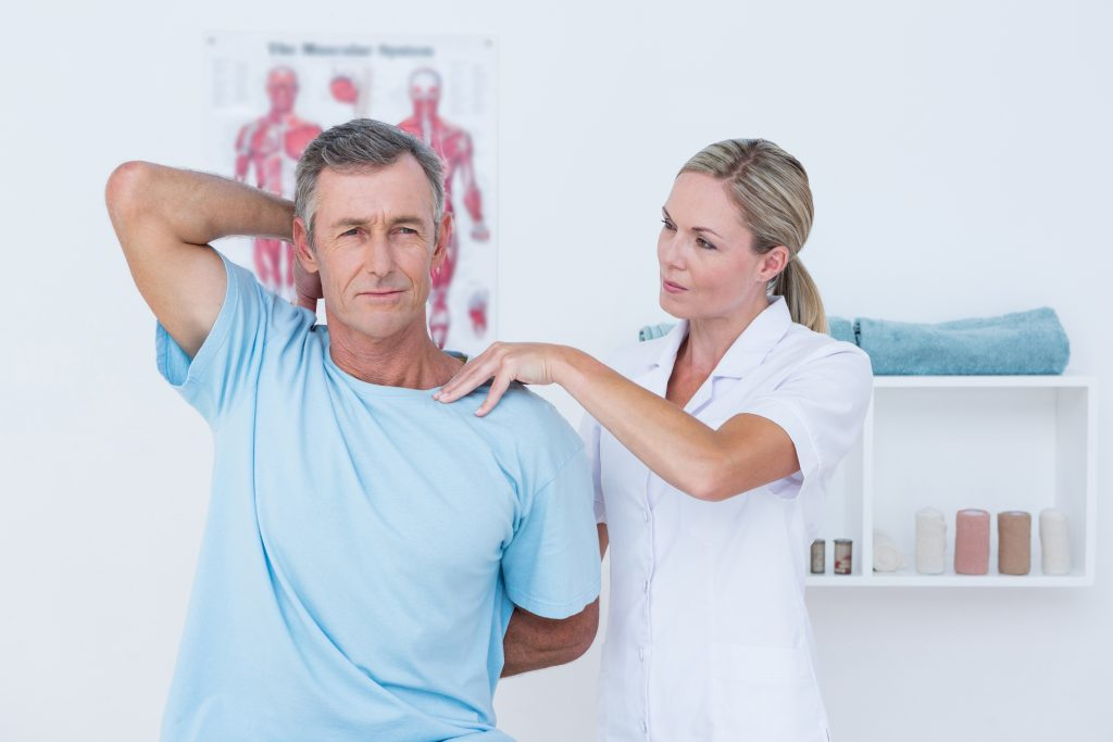 Doctor stretching a man arm in medical office